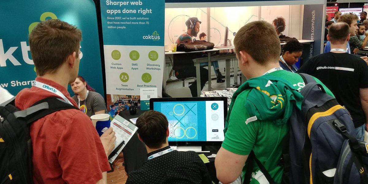 Visitors to the Caktus booth playing Ultimate Tic Tac Toe