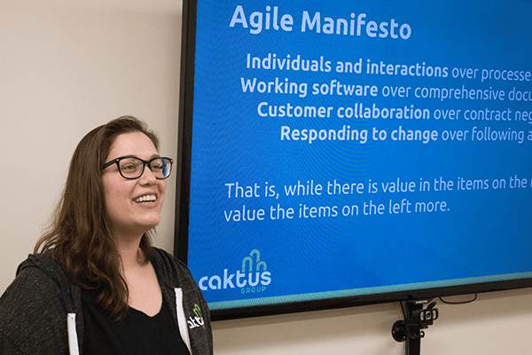 An Agile coach standing in front of a large monitor presenting the Agile Manifesto to clients.