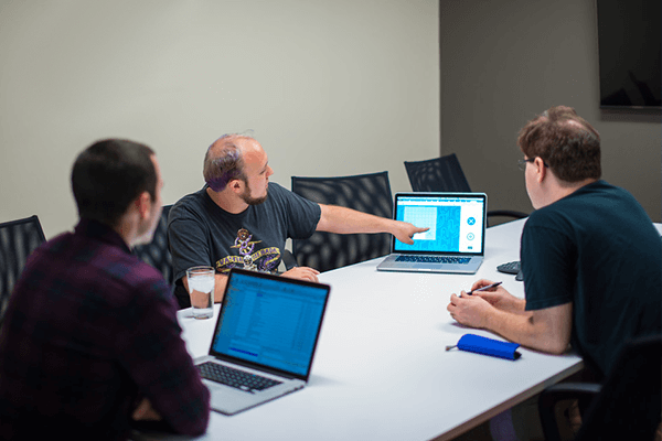 Three developers consulting on Django development in a meeting room.